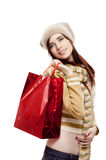 Smiling young female holding shopping bag on white. A vertical portrait of young attractive redhead caucasian female in light-brown hat, scarf and blouse which Royalty Free Stock Image