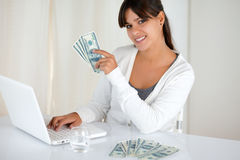 Smiling young female holding up cash money Royalty Free Stock Image