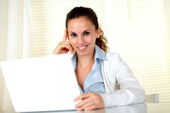 Smiling young female looking at you with laptop Royalty Free Stock Image
