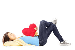 Smiling young female lying down with red heart in her hand Stock Photos