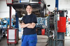 Smiling young female mechanic in garage Stock Photos