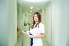 Smiling young female medical professional, doctor with stethoscope and smart phone looking at camera and opening the door to her royalty free stock images