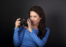 Smiling young female photograph holding photo camera and looking Stock Image