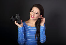 Smiling young female photograph holding photo camera and looking Royalty Free Stock Photo