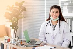 Smiling young female physician wear white coat with stethoscope royalty free stock photo