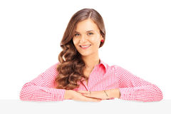 Smiling young female posing behind a blank panel Royalty Free Stock Images