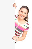 Smiling young female posing on a blank panel Royalty Free Stock Photography