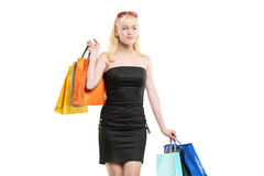 A smiling young female posing with shopping bags royalty free stock images