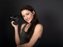 Smiling young female professional photograph holding photo camera and looking happy on dark grey background with empty copy space. Closeup portrait stock photography