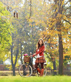 Smiling young female standing with bicycle in park and looking a Royalty Free Stock Photos