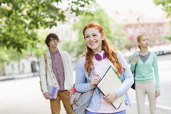 Smiling young female student with friends in background on street Stock Photography