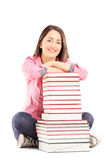 Smiling young female student sitting next to a pile of books Royalty Free Stock Photos