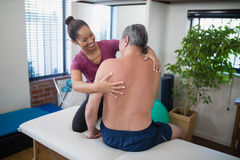 Smiling young female therapist examining back of shirtless senior male patient sitting on bed Stock Photography