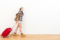 Smiling young female traveler pulling red suitcase. Walking on wooden floor and looking at white wall background ready to travel Royalty Free Stock Images