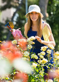 Smiling young female  in uniform at yard gardening Royalty Free Stock Photo