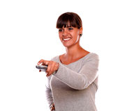 Smiling young female using a tv remote Stock Photography