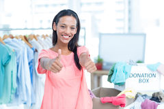 Smiling young female volunteer gesturing thumbs up Stock Photography