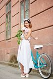 Smiling young female in white dress posing with peonies near blue bike in front of red historical building stock photos