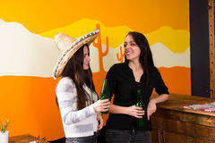Smiling young females drinking beer at bar counter. In Mexican pub stock image