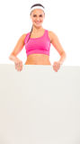 Smiling young fit girl holding blank billboard Stock Photo