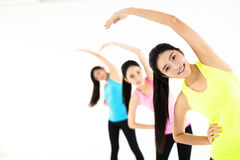 Smiling young fit group stretching in gym Royalty Free Stock Photo