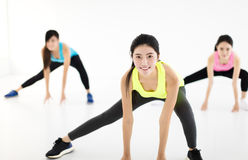 Smiling young fit group stretching in gym Stock Photos