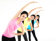 Smiling young fit group stretching in gym Stock Images