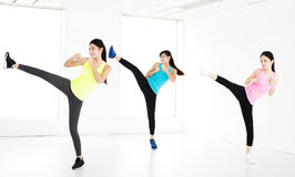 Smiling young fit group stretching and kick Royalty Free Stock Photos