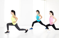 Smiling young fit group stretching and squat Royalty Free Stock Image