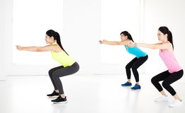Smiling young fit group stretching and squat Stock Image