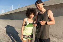 Smiling young fitness couple listening to music Stock Photo