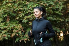 Smiling young fitness woman jogging at the park stock photos