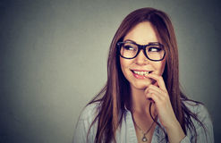 Smiling young flirting woman with finger on lips looking sideways Royalty Free Stock Photo