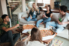 Smiling young friends eating pizza and talking at home. Multiethnic group of smiling young friends eating pizza and talking at home Stock Image