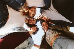 Smiling young friends forming a huddle Royalty Free Stock Photography