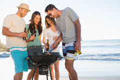 Smiling young friends having barbecue together Stock Image