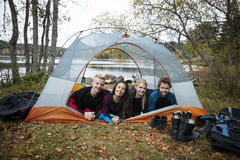 Smiling Young Friends Lying In Tent On Lakeshore Royalty Free Stock Photography