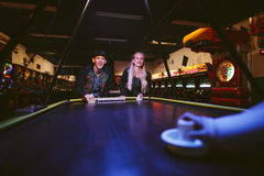 Smiling young friends playing air hockey game Stock Images