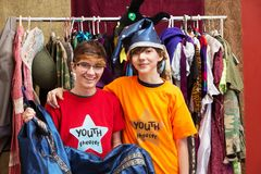 Smiling young friends pose together. In dressing room as one holds his costume Stock Photography