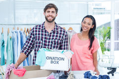 Smiling young friends volunteers separating clothes Royalty Free Stock Photography