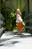 Smiling young girl. Stood on walkway with tropical vegetation in background Royalty Free Stock Image