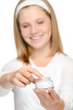 Smiling young girl applying moisturizer cream face Stock Photography