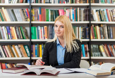 Smiling young girl with blonde hair sitting at a desk in the lib. Rary with an open note book writing out information from books, looking in front, a concept of royalty free stock photography