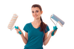 Smiling young girl in the blue shirt stands up straight and holding rollers for painting walls Royalty Free Stock Photos