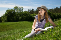 Smiling Young Girl With Book Resting In A Beautiful Field Of Grass Enjoying A Beautiful Sunny Spring Day Stock Photography