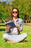 Smiling young girl with book sitting in park Royalty Free Stock Photo