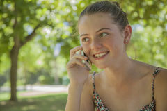 Smiling young girl calling on a cell phone Stock Images