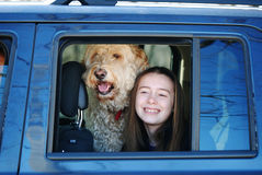 A smiling young girl in a car window with her dog. Royalty Free Stock Images