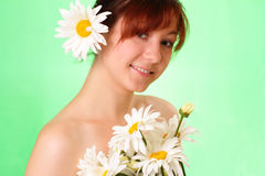 Smiling young girl with chamomile flowers Royalty Free Stock Image