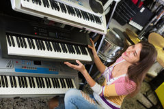 Smiling young girl choosing synthesizer Royalty Free Stock Photography